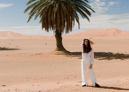 a lady standing in the desert, with palmstrees in the background