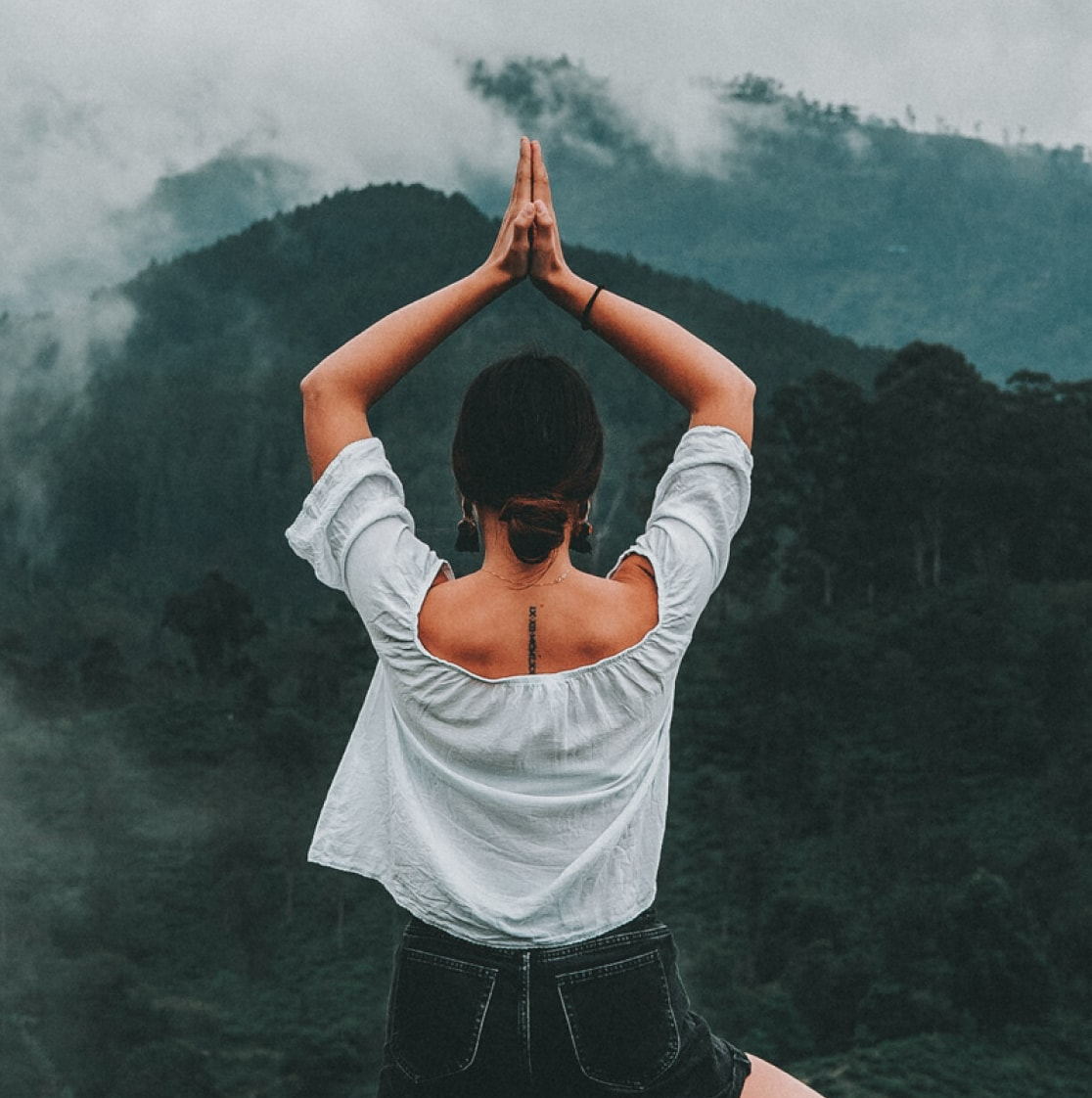 a girl doing yoga with hills in the background